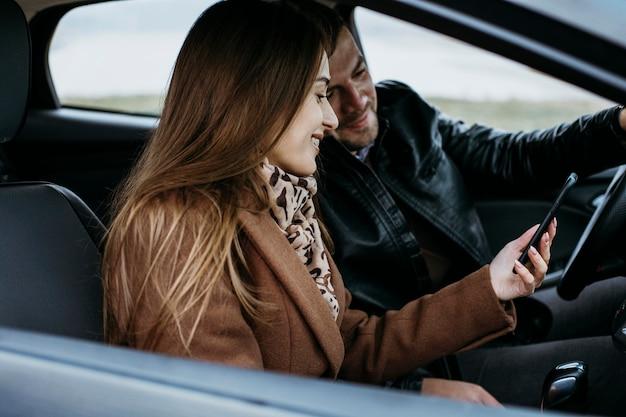Vista lateral de casal usando smartphone no carro