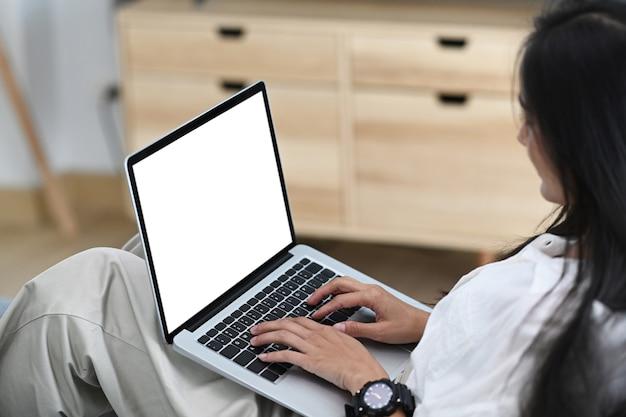 Vista lateral de casual mulher asiática usando laptop enquanto está sentado no sofá em casa.