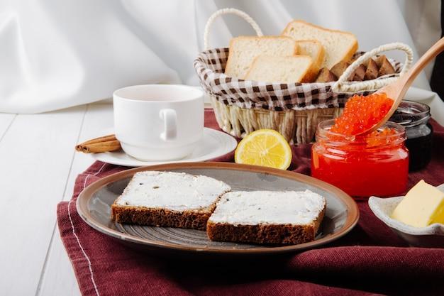 Vista lateral de caviar vermelho e preto com torradas em um prato com manteiga e uma xícara de chá numa toalha de mesa vermelha