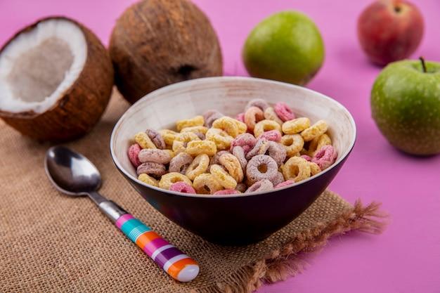 Vista lateral de cereais coloridos em uma tigela com colher com cocos e maçã verde no pano de saco na superfície rosa