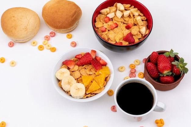 Vista lateral de cereais de café da manhã com morango e café na superfície branca horizontal