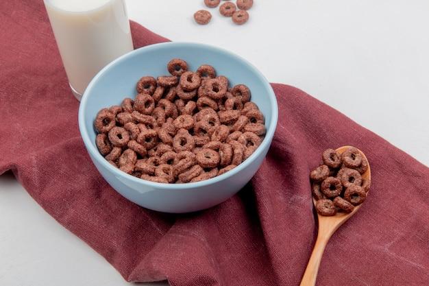 Vista lateral de cereais na tigela e na colher de pau com leite no pano de bordo e superfície branca