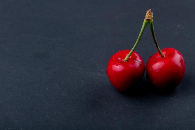Vista lateral de cereja madura vermelha isolada no preto, com espaço de cópia