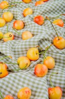 Vista lateral de cerejas amarelas em pano xadrez