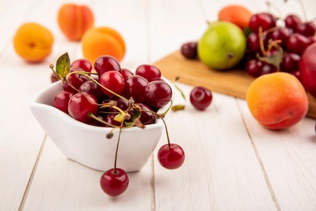 Vista lateral de cerejas em uma tigela com frutas como pêssego e cereja de pêra na tábua e no fundo de madeira