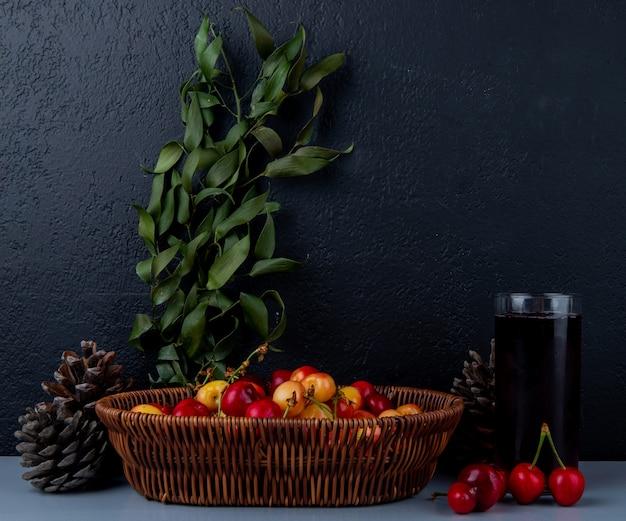 Vista lateral de cerejas maduras mais chuvosas em uma cesta de vime com um copo de suco de cereja e folhas verdes no escuro