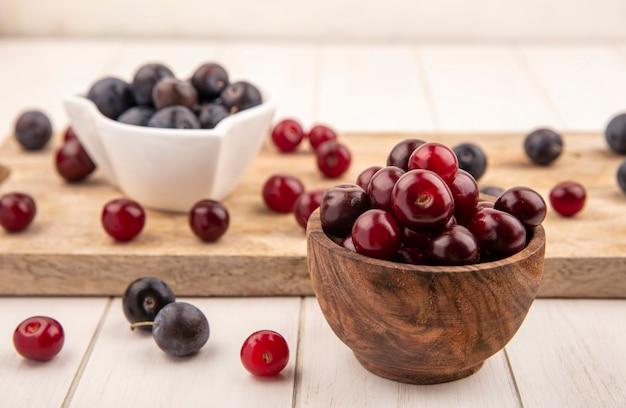Vista lateral de cerejas vermelhas em uma tigela de madeira com abrunhos roxos escuros em uma tigela branca em uma placa de cozinha de madeira em um fundo branco de madeira