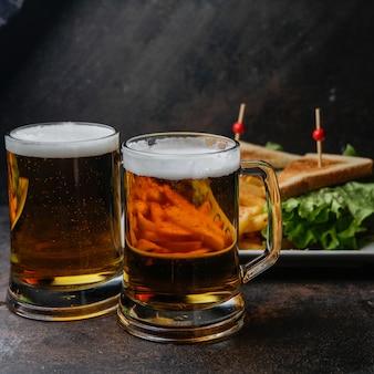 Vista lateral de cerveja com um prato de sanduíche e batatas fritas
