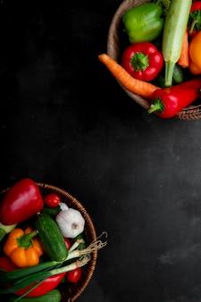 Vista lateral de cestas cheias de legumes como pepino cenoura pimenta cebolinha e outros nos lados direito e esquerdo e superfície preta