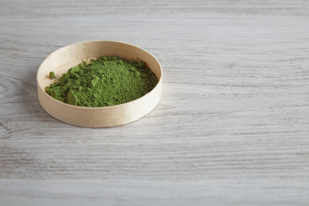Vista lateral de chá matcha orgânico premium em pó em uma caixa de madeira isolada na mesa branca simples