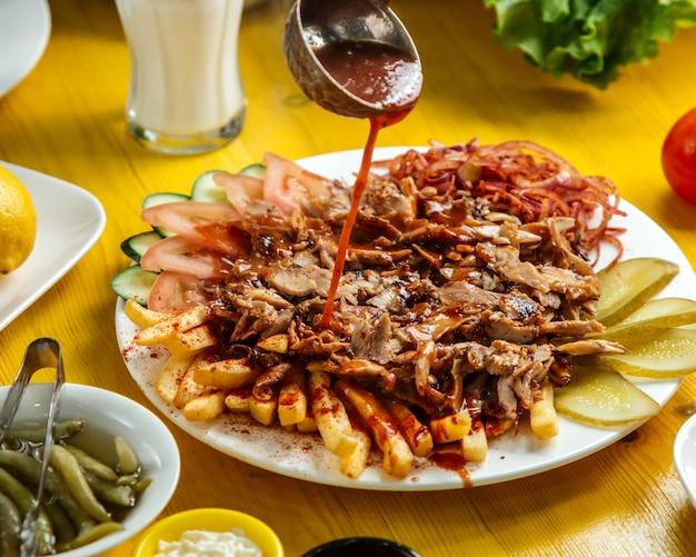 Vista lateral de chiken doner kebab no prato com pão batatas fritas tomates pickles de cebola e salada