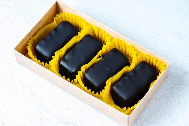 Vista lateral de chocolate doces em uma embalagem amarela em uma caixa