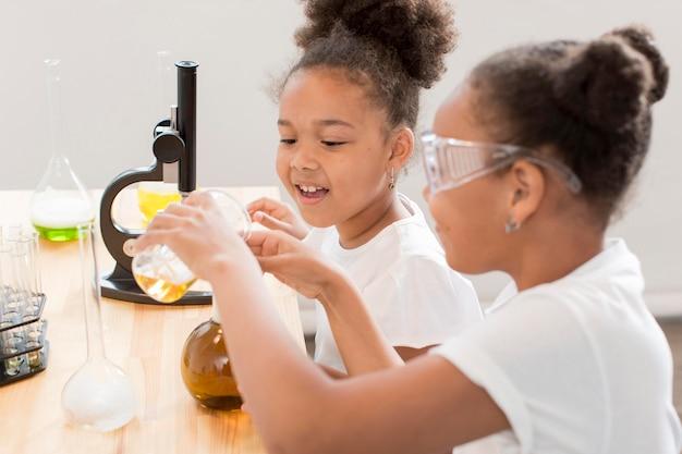 Vista lateral de cientistas garota em casa com óculos de segurança e microscópio