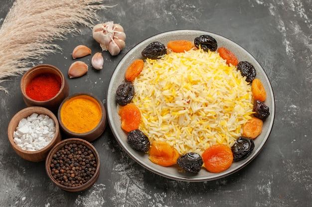 Vista lateral de close-up arroz arroz com frutas secas e alho tigelas de especiarias