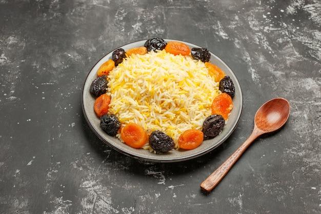 Vista lateral de close-up arroz colher de pau frutas secas e arroz no prato sobre a mesa