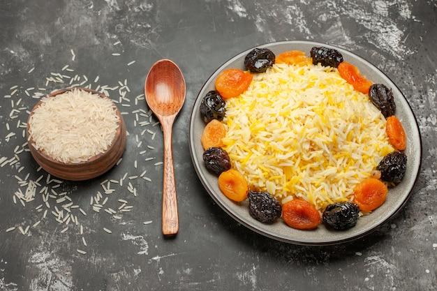 Vista lateral de close-up arroz o apetitoso arroz com frutas secas colher tigela de arroz