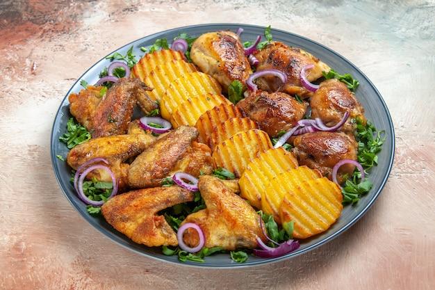 Vista lateral de close-up asas de frango as apetitosas batatas asas de frango cebola ervas