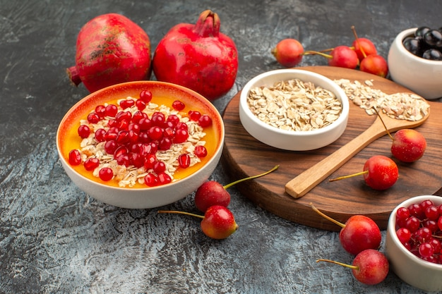 Vista lateral de close-up aveia colher de aveia na tábua de corte as apetitosas frutas vermelhas romã