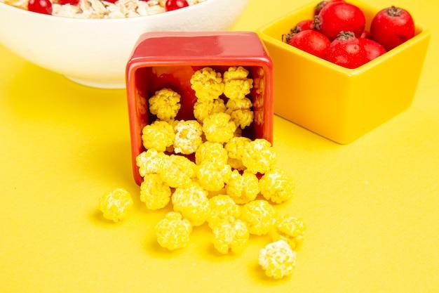 Vista lateral de close-up bagas doces amarelos bagas coloridas nas taças sobre a mesa
