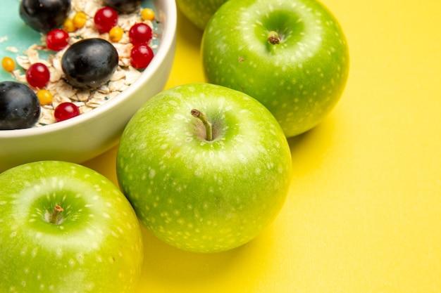 Vista lateral de close-up bagas tigela de groselha uvas pretas aveia maçãs verdes