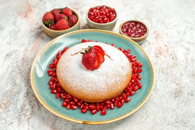 Vista lateral de close-up bolo apetitoso bolo apetitoso de morangos e romã e as tigelas de frutas vermelhas na mesa