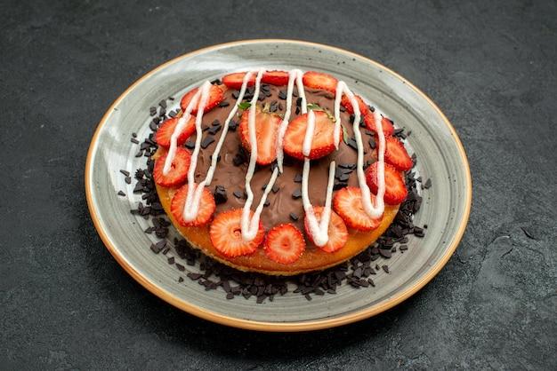 Vista lateral de close-up bolo apetitoso com pedaços de chocolate e morango no prato no centro da mesa escura