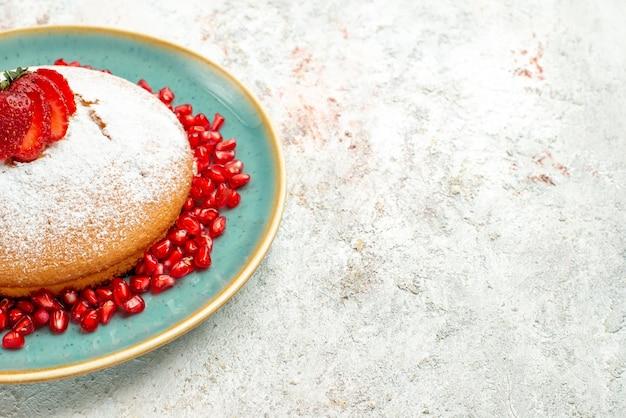 Vista lateral de close-up bolo apetitoso de romã de morango com morangos e romã na mesa cinza-rosa