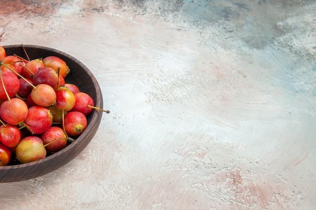 Vista lateral de close-up cerejas as cerejas apetitosas na tigela de madeira sobre a mesa