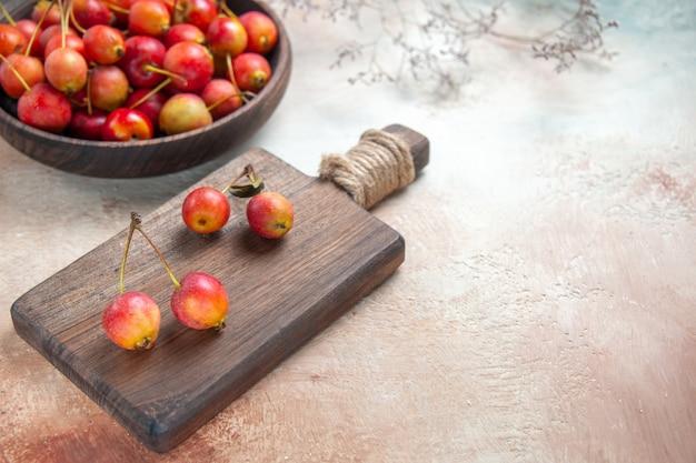 Vista lateral de close-up cerejas na mesa da cozinha com bagas tigela de galhos de árvore