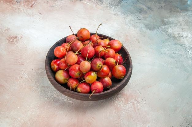 Vista lateral de close-up cerejas tigela de madeira com cerejas vermelhas e amarelas em cima da mesa