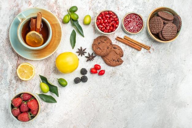 Vista lateral de close-up chá com biscoitos de frutas vermelhas a xícara de chá com limão, morango e frutas cítricas em cima da mesa