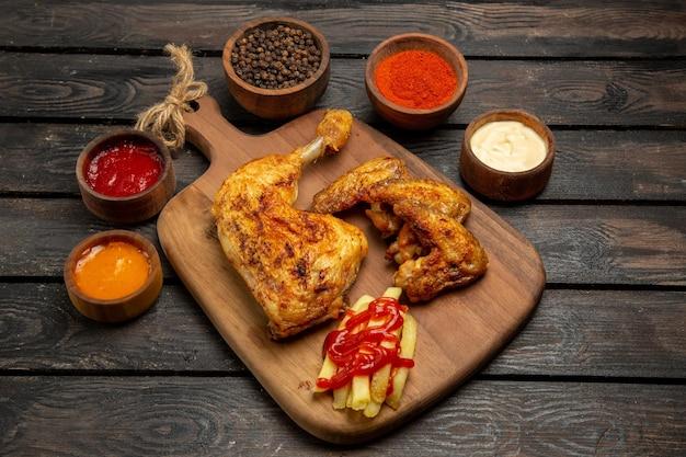 Vista lateral de close-up com batatas fritas, coxa e asas de frango, batatas fritas e tigelas com molhos e temperos coloridos