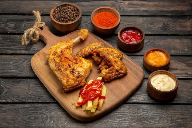 Vista lateral de close-up com batatas fritas, frango, batatas fritas e tigelas com molhos coloridos e temperos na mesa escura