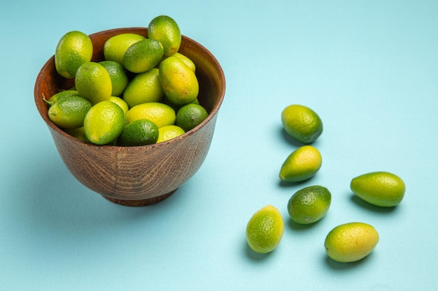Vista lateral de close-up com frutas castanhas tigela de frutas verdes na superfície azul