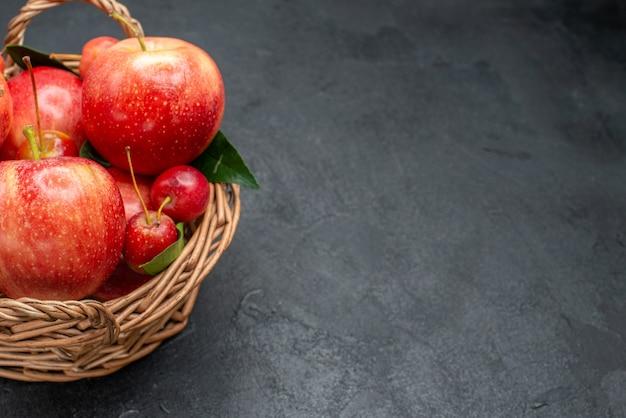 Vista lateral de close-up com frutas, cerejas e maçãs com folhas na cesta sobre a mesa