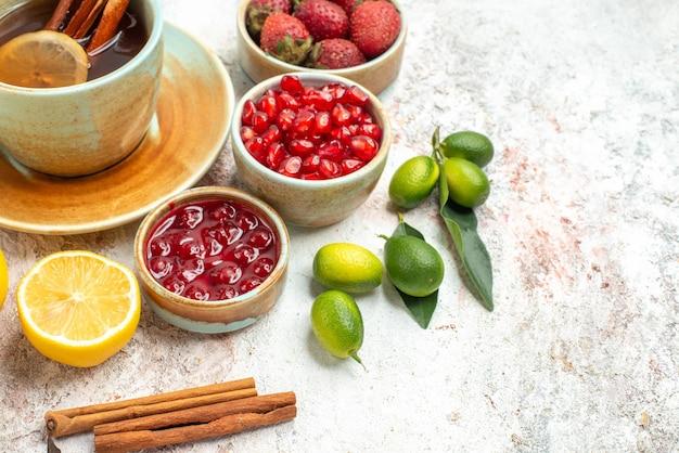 Vista lateral de close-up com frutas e chá uma xícara de chá de limão, geléia de morangos e canela