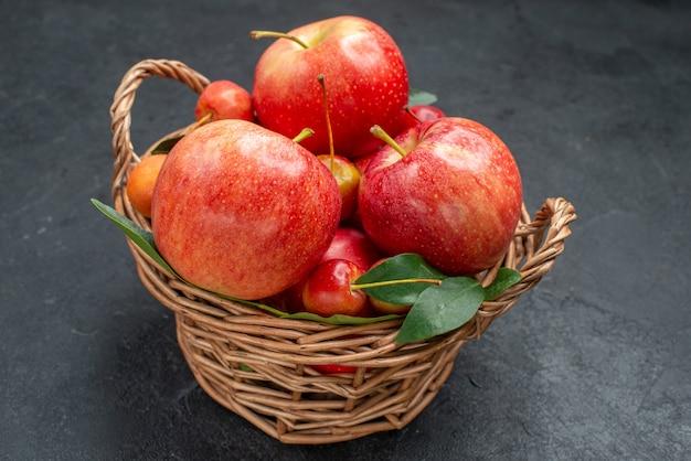 Vista lateral de close-up com frutas, maçãs e cerejas com folhas na cesta na mesa escura
