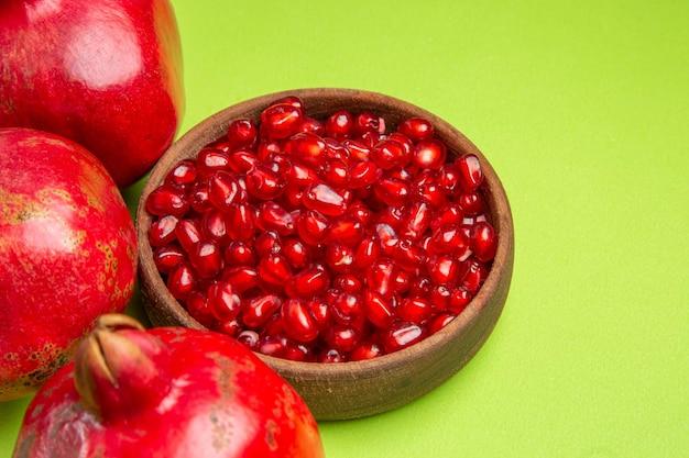 Vista lateral de close-up com frutas na tigela marrom das apetitosas sementes de romã na mesa verde