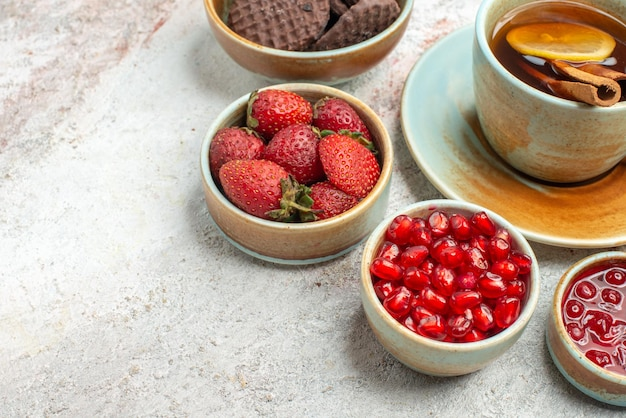 Vista lateral de close-up com frutas, uma xícara de chá preto, romã, tigelas com biscoitos de frutas vermelhas na mesa