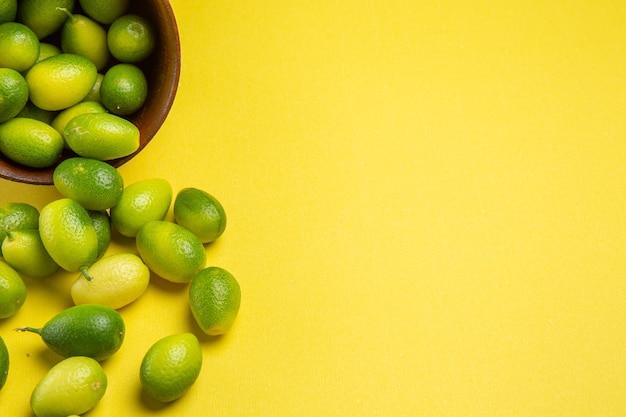Vista lateral de close-up com frutas verdes tigela marrom das frutas verdes apetitosas na mesa