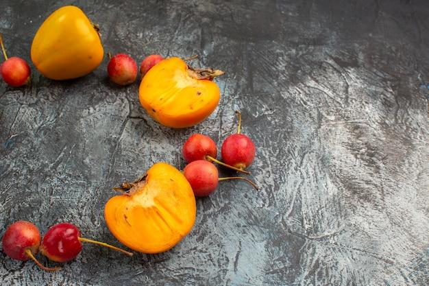 Vista lateral de close-up com frutas vermelhas e apetitosas cereja meio caqui na mesa cinza