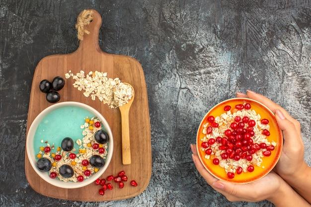 Vista lateral de close-up com frutas vermelhas e bagas de aveia na tigela de mingau de aveia com romã nas mãos