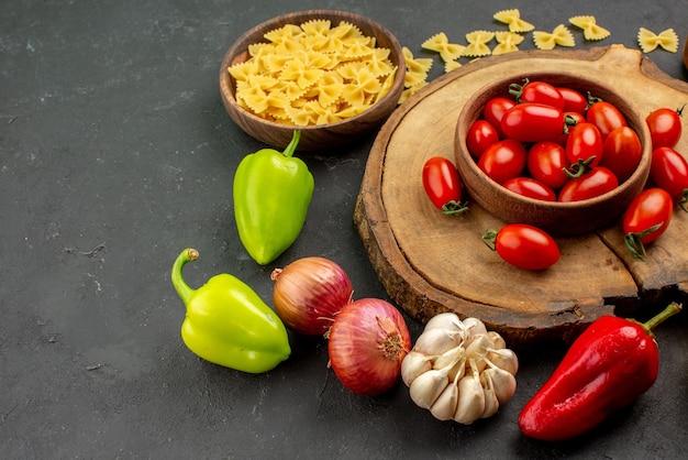 Vista lateral de close-up com macarrão saboroso com alho, cebola e pimentão ao lado da tigela de tomates na tábua de madeira