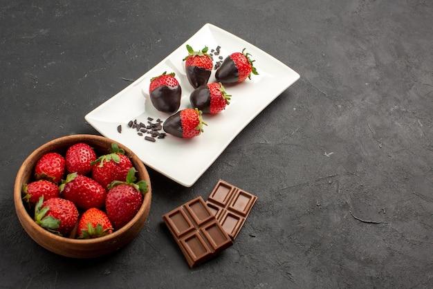 Vista lateral de close-up com morangos com cobertura de chocolate tigela de morangos e barras de chocolate ao lado do prato de morangos com cobertura de chocolate na mesa escura