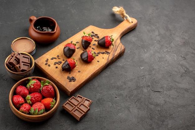 Vista lateral de close-up com morangos com creme de chocolate e morangos com cobertura de chocolate e creme de chocolate na tábua da cozinha na mesa escura