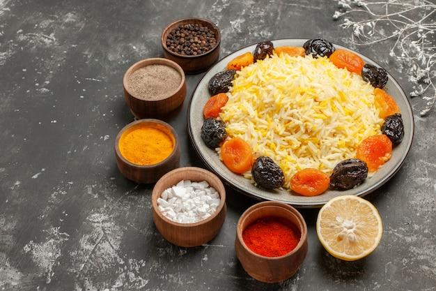 Vista lateral de close-up de arroz, limão, tigelas, prato de especiarias, arroz com frutas secas