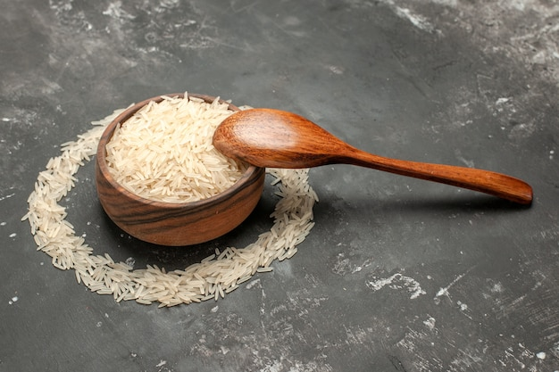 Vista lateral de close-up de arroz tigela de arroz marrom ao lado da colher na mesa escura