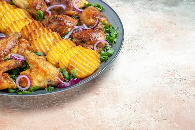 Vista lateral de close-up de asas de frango as apetitosas asas de frango com batatas ervas e cebolas