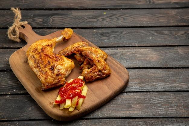 Vista lateral de close-up de batatas fritas, batatas fritas e apetitoso frango com ketchup na tábua de cortar na mesa de madeira