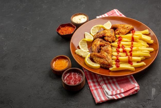 Vista lateral de close-up de comida em um prato de laranja, batatas fritas apetitosas asas de frango com limão e ketchup e tigelas de molhos e especiarias em uma toalha de mesa quadriculada rosa-branca à direita